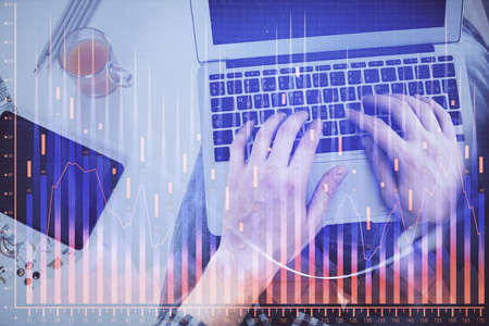 Double exposure of mans hands typing over laptop keyboard and forex chart hologram drawing. Top view. Financial markets concept. 免版税图像