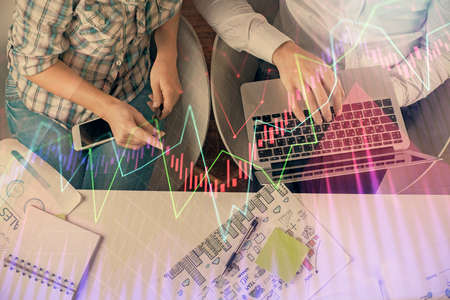 Multi exposure of man and woman working together and forex graph hologram drawing. Financial analysis concept. Computer background. Top View.