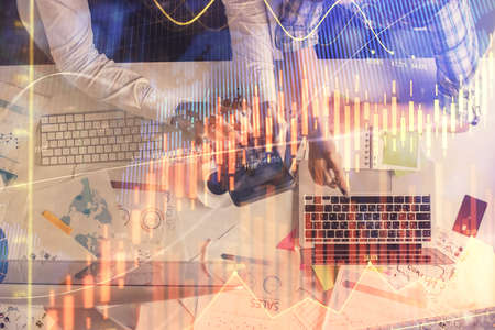 Double exposure of man and woman working together and financial graph hologram drawing. market analysis concept. Computer background. Top View. 免版税图像