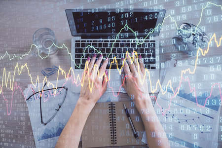 Double exposure of woman hands working on computer and forex graph hologram drawing. Top View. Financial analysis concept. 免版税图像