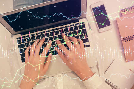 Double exposure of woman hands working on computer and forex chart hologram drawing. Top View. Financial analysis concept.