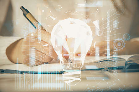 Bulb hologram over hands taking notes background. Concept of idea. Double exposure