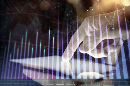 Double exposure of mans hands holding and using a digital device and forex graph drawing. Financial market concept. 版權商用圖片