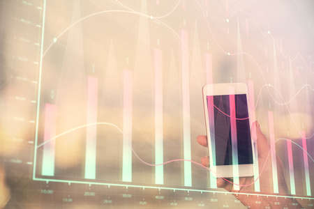 Double exposure of forex chart sketch hologram and woman holding and using a mobile device. Stock market concept. 版權商用圖片