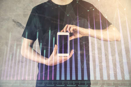 Double exposure of mans hands holding and using a digital device and forex graph drawing. Financial market concept. 免版税图像