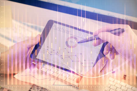 Double exposure of mans hands holding and using a phone and financial chart drawing. Market analysis concept.