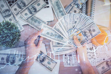 Multi exposure of financial graph drawing hologram and USA dollars bills and man hands. Analysis concept.