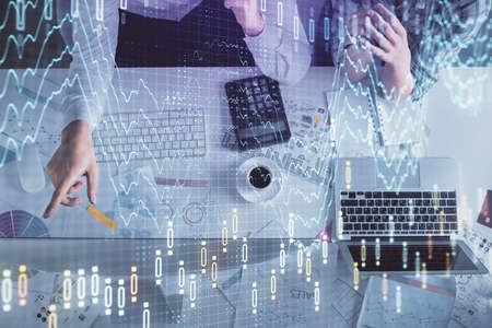 Double exposure of man and woman working together and financial graph hologram drawing. market analysis concept. Computer background. Top View.