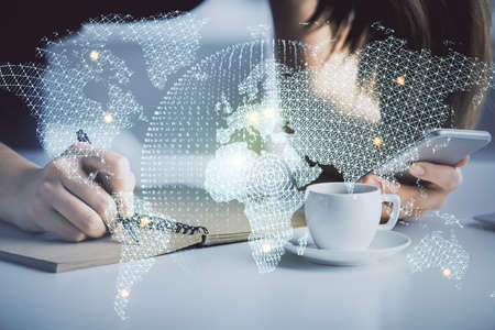 Double exposure of business theme sketch hologram and woman holding and using a mobile device.