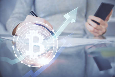 Double exposure of blockchain business sketch hologram and woman holding and using a mobile device.