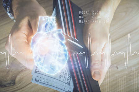 Multi exposure of heart drawing hologram and USA dollars bills and man hands. Medical education