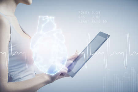 Double exposure of heart sketch hologram and woman holding and using a mobile device. Medical education concept.