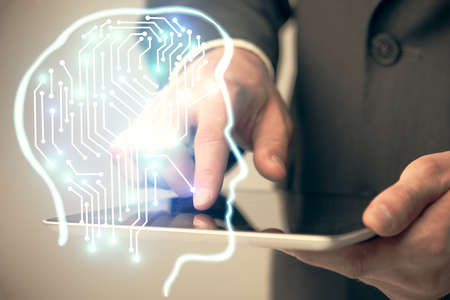 Double exposure of man's hand holding and using a digital device and brain hologram drawing. Data concept.