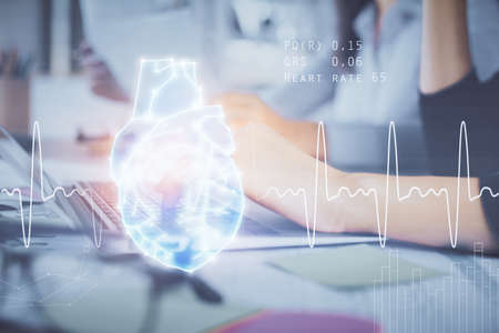Double exposure of woman hands typing on computer and heart hologram drawing. Education concept.