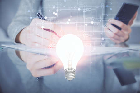 Double exposure of light bulb hologram and woman holding and using a mobile device. Idea concept. Stock Photo
