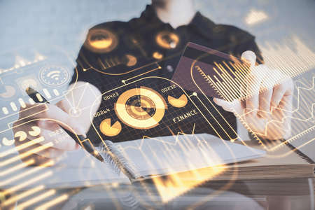Double exposure of man hands holding a credit card and tech theme drawing. Technology in E-commerce concept. 免版税图像
