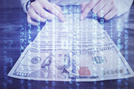 Double exposure of technology drawing hologram and us dollars bills and man hands. Data concept