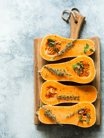 Fresh orange muscat pumpkin, cut in half, ready for baking with spices and herbs
