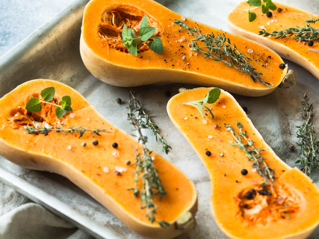 Orange fresh pumpkin cooking with spice and herbs. cut pumpkin slices on a baking sheet.