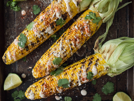 Grilled corn cobs with sauce, coriander, lime, paprika and cheese. Mexican food. Top view