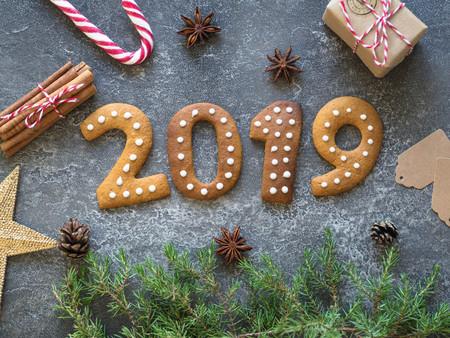 Galletas de jengibre de Navidad o año nuevo en forma de números 2019 sobre un fondo oscuro.Envases de temporada y atributos de Año Nuevo. Foto de archivo