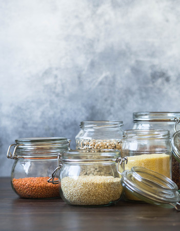 Open glasses jars with pasta, lentils, couscous, beans and quinoa on table