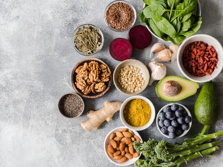 Cibo sano e pulito - verdure, frutta, noci, supercibi su sfondo grigio. Mangiare sano concetto.