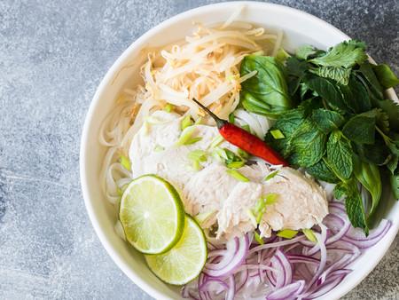 Tradycyjna wietnamska zupa ga w białej misce z makaronem drobiowym i ryżowym, miętą i kolendrą, zieloną i czerwoną cebulą, chili, kiełkami fasoli i limonką na szarym tle.