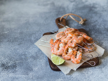 Red shrimps on metal skewers with lime juice on wood board on grey background.