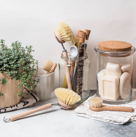 Concept zéro déchet. Ensemble de cuisine écologique. Brosses, savon en pot, épices en tubes de verre et plante en pot de fleurs en bois Banque d'images