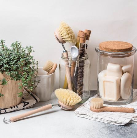 Geen afvalconcept. Milieuvriendelijke keukenset. Borstels, zeep in pot, kruiden in glazen buizen en plant in houten bloempot Stockfoto