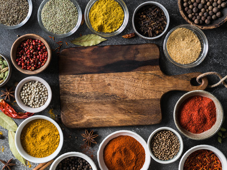 Various dry spices flat lay in small bowls and wood board on gray