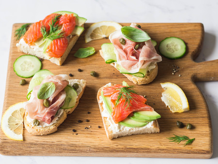 Sandwiches with cream cheese, salmon, avocado and cream cheese, prosciutto, cucumber on grilled toasts on wood board