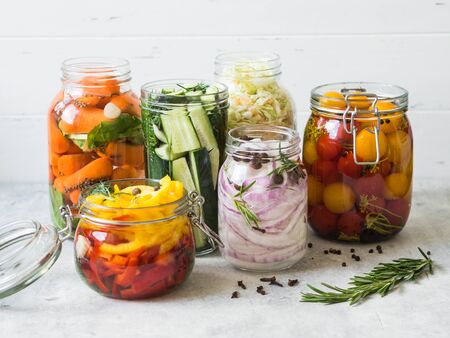 Salting various vegetables in glass jars for long-term storage.