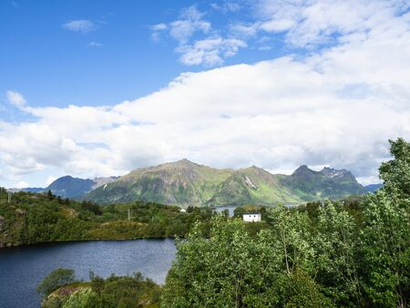 View of low mountains with sharp peaks, lakes and a white wooden house in Norway