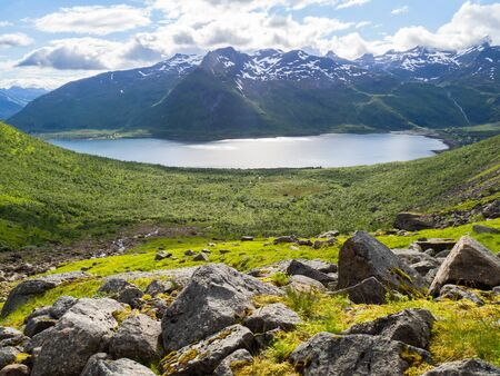 Norwegian landscape with green valley between mountains with snow peaks. Фото со стока