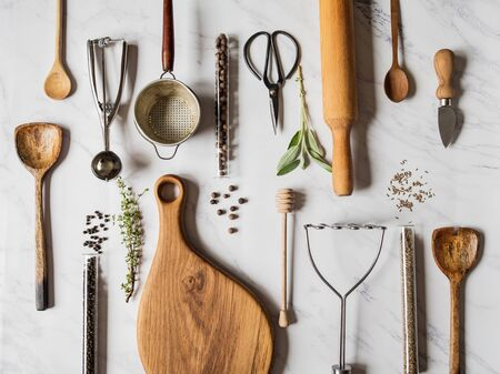 Flat lay various metal, wooden kitchen tools and dry spices in glass tube and raw herbs on marble background. Top view.