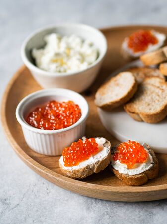 Sandwiches with cream cheese and red caviar on large wooden tray and ingredients in bowls Archivio Fotografico
