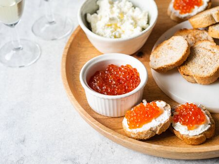 Sandwiches with cream cheese and red caviar on a large wooden tray and ingredients in bowls