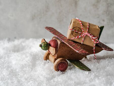 Christmas composition with a wooden vintage plane carrying a Christmas holiday gift Banque d'images