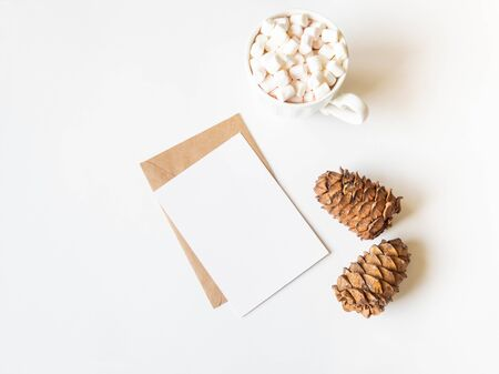 White mug with hot drink and marshmallows, paper card for letter, envelope and two cedar cones on white background. Top view. Copy space