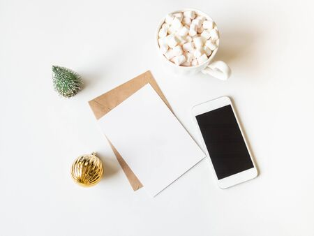 White mug with hot drink and marshmallows, paper card for letter, envelope, white phone and xmas decoration on white background. Top view. Copy space