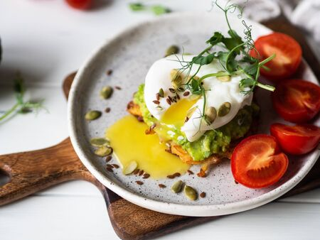 Healthy nutritious breakfast of potato pancake, mashed avocado, poached egg, pea sprouts and various seeds on ceramic plate