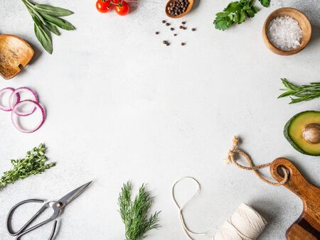 Fresh raw greens, vegetables, spices and kitchenwere frame on grey background. top view, copy space.