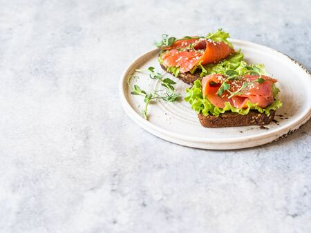Two toasts with salmon slices, sesame, pea sprouts and lettuce on a white ceramic plate on grey background.