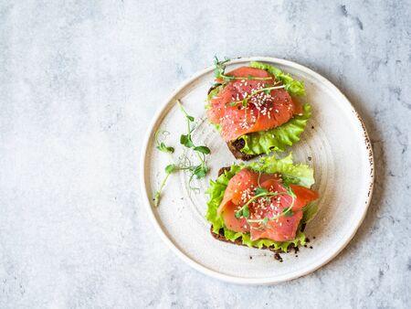 Due toast con fette di salmone, sesamo, germogli di pisello e lattuga su un piatto di ceramica bianca su sfondo grigio. Copia spazio.
