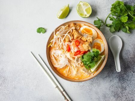 Malaysian noodles laksa soup with chicken, prawn and tofu in a bowl on grey background. Top view. Copy space