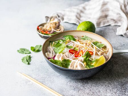 Traditional Vietnamese soup- pho ga in bowl with chicken and rice noodles, mint and cilantro, red onion, chili, bean sprouts and lime on grey background. Asian food.