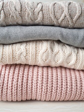 Stack of warm knitted woolen sweaters pastel shades background