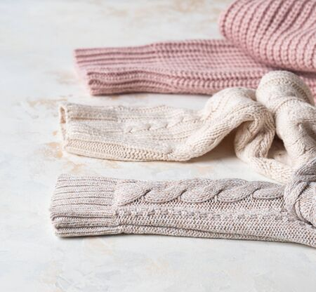 Sleeves of three of warm different knitted woolen sweaters pastel shades